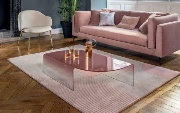 glass coffee table next to pink couch